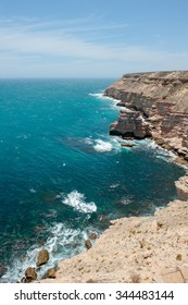 Scenic Aerial panorama of  rugged rock cliff coast formation of Kalbarri National Park in Western Australia, wild sea of Indian Ocean, blue sky, horizon, copy space.