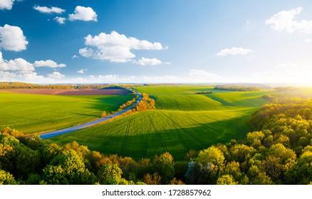 Landschaftsfotografie der Landstraße durch landwirtschaftliche Flächen und Grünflächen. Drohnenschuss in der oberen Ansicht. Agrar-Gebiet der Ukraine, Europa. Konzept der Agrarindustrie. Schönheit der Erde.