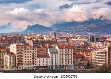 Scenic aerial view of the banks of the Isere river, roofs and French Alps on the background, Grenoble, France