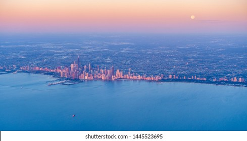 Scenic aerial view of full moon setting over Chicago downtown at sunrise
