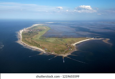 scenic aerial view of the German island Wangerooge in the North Sea with vivid blue sky and clouds while low tide