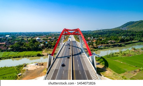 Scenic Aerial View of Kalikuto Bridge, an Iconic Red Bridge at Trans Java Toll Road, Batang, Central Java, Indonesia