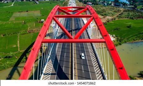 Scenic Aerial View of Kalikuto Bridge, an Iconic Red Bridge at Trans Java Toll Road, Batang, Central Java, Indonesia