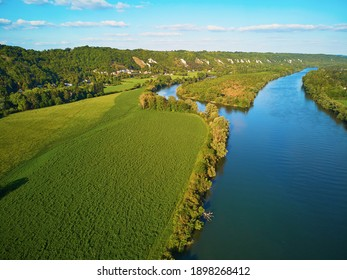 Scenic aerial view of the Seine river and green fields in French countryside. Val d'Oise department, Ile-de-France, Northern France