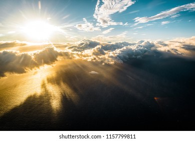 Scenic Aerial View of Sun Rays Coming through Clouds Over Pacific Ocean at Sunrise with Abstract Shadows Cast on Blue Water