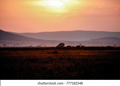 scenic african sunset in the safari national park serengeti in tanzania with great colors of the grassland, some dust in the air and a amazing mountain range in the background
