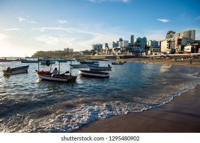 Scenic afternoon view of traditional Brazilian fishing boats anchored off the shore of Rio Vermelho beach, a coastal neighborhood in Salvador, Bahia, Brazil
