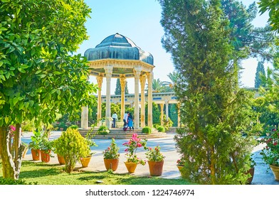 The scenic alcove of Hafez Tomb with carved stone columns and lush greenery of Mussala Gardens around it, Shiraz, Iran.