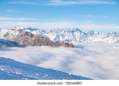 Scenic alpine landscape, clouds on the valley arisign mountain peaks sunset light, winter snow.