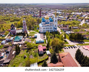 Scenic architectural ensemble of ancient Savior Transfiguration Cathedral and Trinity Church with extended bell tower on Bolkhov cityscape background, Russia