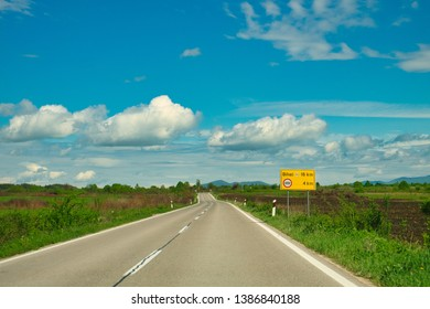 A scenic asphalt road in the green meadows and blue sky with white clouds on the way from Croatia to Bihac, Bosnia and Herzegovina