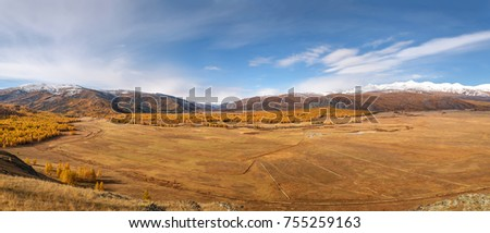 Scenic autumn aerial view on mountains covered with forest and snow, steppe and golden trees against a background of clouds and blue sky