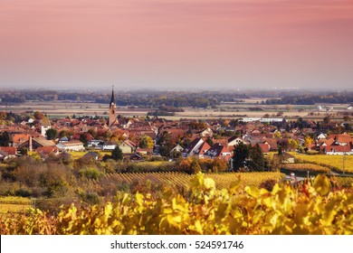 Scenic autumn landscape with a historic village in Alsace, France, and vineyards growing in the mountains. Colorful travel and wine-making background.