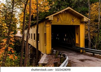 A scenic autumn view of the historic and restored WIndsor Mills covered lattice through truss bridge in Ashtabula County, Ohio.