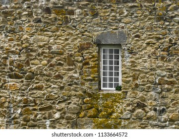 Scenic background of a window in the stone wall of the William Henry Fort in New Harbor, Maine.  It is slightly ajar and a plant has spotted in the windowsill.