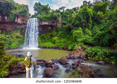 Scenic basaltic rock formations famous waterfalls Iguazu Falls. Energetic woman with a tourist backpack pictures a waterfall. Concept of active and phototourism