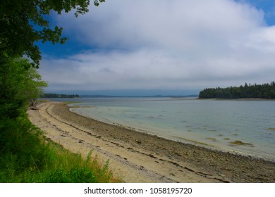 Scenic beach and island along the Maine coast with blue sky and white clouds