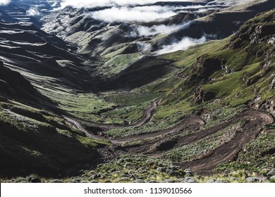 A scenic and beautiful view down a long and steep curvy dirt road twisting up the mountain above the clouds through green grass covered hills and mountains with a blue sky and rocks in the foreground