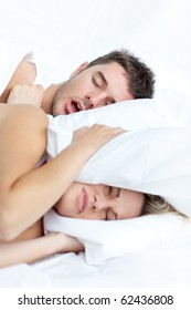 Scenic in bedroom of young couple lying in bed and holding pillow on the ears because of snoring boyfriend.