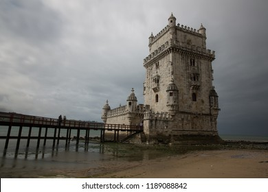 Scenic Belem Tower and wooden bridge miroring with low tides on Tagus River.Lisbon