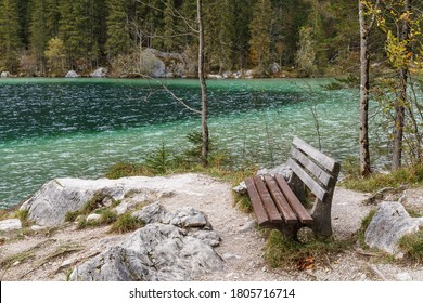 Scenic bench with boulders on the shore of the mountain lake Hintersee in Bavaria, Germany. Ramsau bei Berchtesgaden.