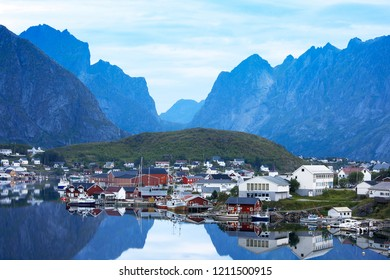 Scenic blue archipelago landscape with mountains and fishman's houses in the smooth water in fishing Norway village, Lofoten island, Hamnoy in summer time, white nights.