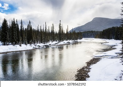 Scenic Bow River with Snow Covered Banks on a Freezing Cloudy Winter Day. Banff National Park, AB, Canada.