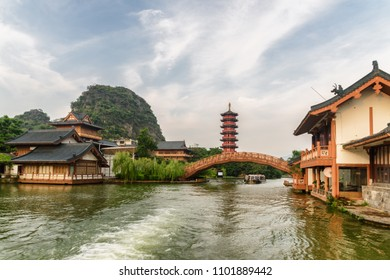 Scenic bridge over lake and traditional Chinese wooden houses in Guilin, China. Amazing karst mountains and beautiful red pagoda are visible on blue sky background.