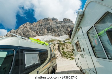 Scenic Camper Vans Camping. Two Motohomes and the Alpine Scenery. Small Class A Motoroaches Rving in High Mountains.