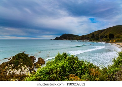 Scenic Cannibal Bay. Pacific coast of the South Island. New Zealand. Powerful ocean surf, white sand beach and blue-green water. The concept of ecological, active and phototourism