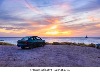 Scenic caribbean sunset with a car near a cliff and a boat at the horizon