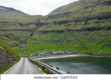 Scenic coastal road leads to tranquil oceanfront village in spectacular Faroe Islands. Amazing view of the beachfront houses hidden under the towering grassy mountains. Stunning Scandinavian landscape