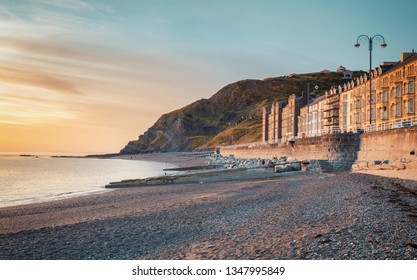 Scenic coastal town in warm sunset light at low tide. Aberystwyth in Wales, UK