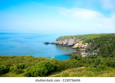 Scenic coastal view. Fog over the ocean in the distance. Blue ocean and sky. Trees and cliff. Taken at Cape Spencer, NB, Canada.
