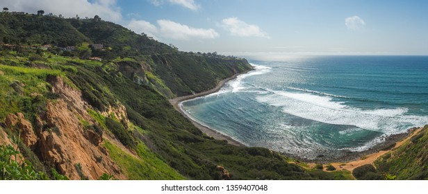 Scenic coastal view of tall cliffs of Bluff Cove covered with vegetation on a sunny spring day with  turquoise colored water and rocky beach, Blufftop Trail, Palos Verdes Estates, California