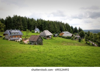Scenic countryside landscape in the Black Forest: green summer mountain valley with forests, fields and old houses in Germany