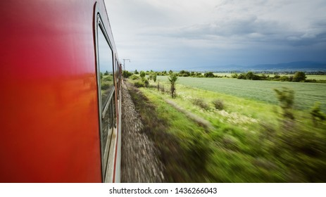 Scenic countryside view from the window of a moving train with motion blur.