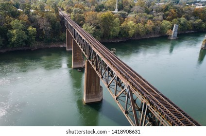 Scenic Daytime Aerial Drone Outdoor Photography Looking Down at Vintage Rust Covered Old Steel Concrete Railroad Train Track Crossing Historic Potomac River in Maryland, USA