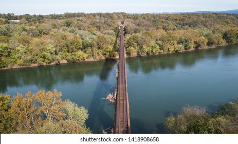 Scenic Daytime Aerial Landscape Photograph Looking Down Rusty Old Vintage Antique Steel Train Track Crossing Historic Potomac River in Maryland, USA