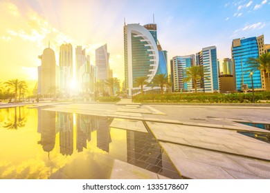 Scenic Doha West Bay high rises at sunset light reflecting in the water of park in Downtown. Modern skyscrapers of Doha skyline in Qatar, Middle East, Arabian Peninsula in Persian Gulf.