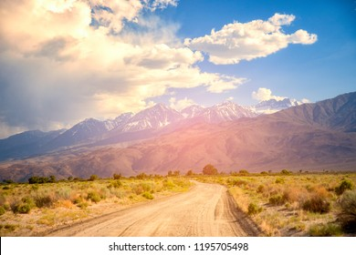 Scenic Drive on Dirt Road through Eastern Sierra Mountain, Travel concept with big 4x4 car against sunset and mountains.