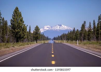 Scenic empty asphalt road leading towards a distant mountain