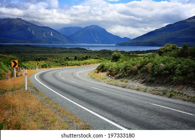 Scenic empty road in New Zealand. Mountains and a lake in the background.