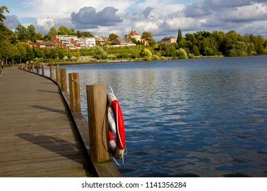 A scenic and empty wooden pier at the swedish lake Trummen in Vaxjo, in the region Smaland, Sweden on a sunny day with some clouds on the sky. Vaxjo is know as the greenest city in Europe