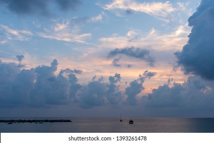 scenic evening view with a boat in a calm sea and dramatic clouds