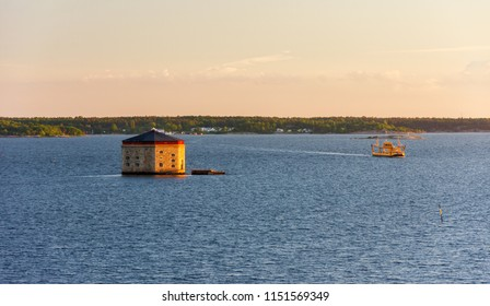 Scenic evening view on Godnatt naval keep (fortress in the sea for defense of naval harbor) and vessel in the Baltic Sea near Karlskrona, Sweden. Part of the UNESCO World Heritage Site Karlskrona.