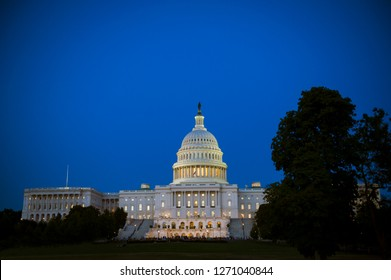 Scenic evening view of the US Capitol Building with glowing lights under blue dusk sky in Washington DC, USA