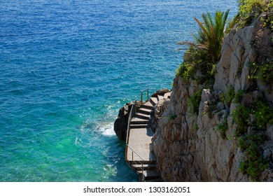 Scenic Fisherman Cove in Monaco / Monte-Carlo: steps leading into colorful ocean (with space for text)