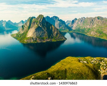 Scenic fjord landscape with Reine village, coast nature with sharp high mountain peaks, Lofoten islands North Norway. Travel destination.