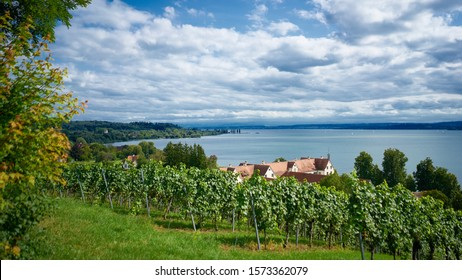 Scenic German landscape with dramatic sky, vineyards and homes with red tiled roof overlooking Lake Constance or Bodensee.  Far shore is Switzerland.